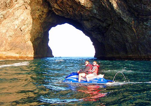 Couple jet-skiing, Hole in the Rock Bay of Islands