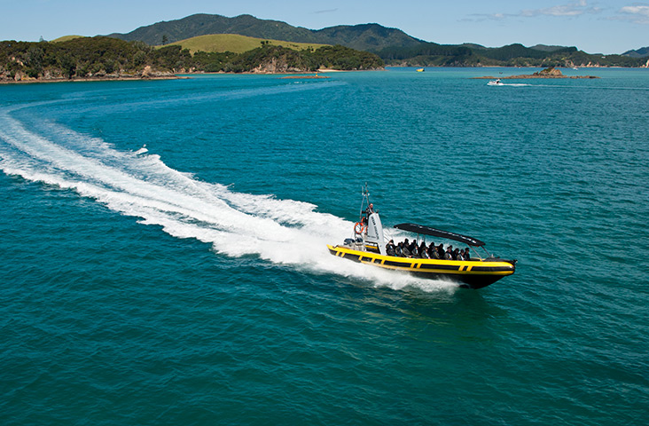 boat cruising through islands on ocean adventure, bay of islands